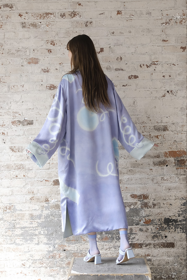 The robe features a quilted neckline and waist tie. It is fully lined in a celadon green silk charmeuse. The pattern continues unbroken across seam lines.