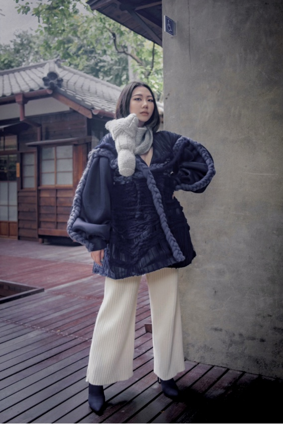 Three-piece ensemble, with drop-shoulder blouson sleeve coat, handknit horsehead scarf, and wide-leg pants, juxtaposed against a traditional Japanese architectural background.