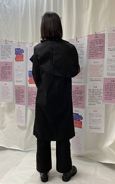 Photo 3 -  A black coat with asymmetrical lapels and a typography pants with red threads embroidery (back view)