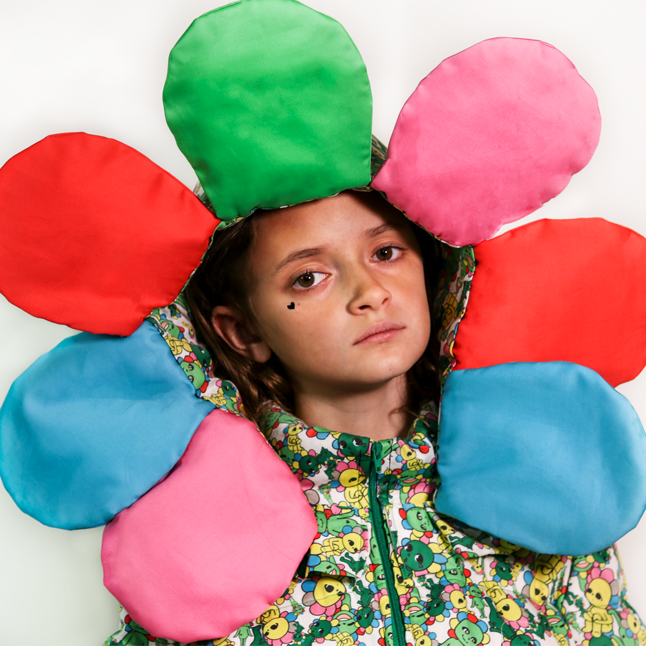 Close up view of the model wearing the puffer jacket with the detachable flower petal hood.