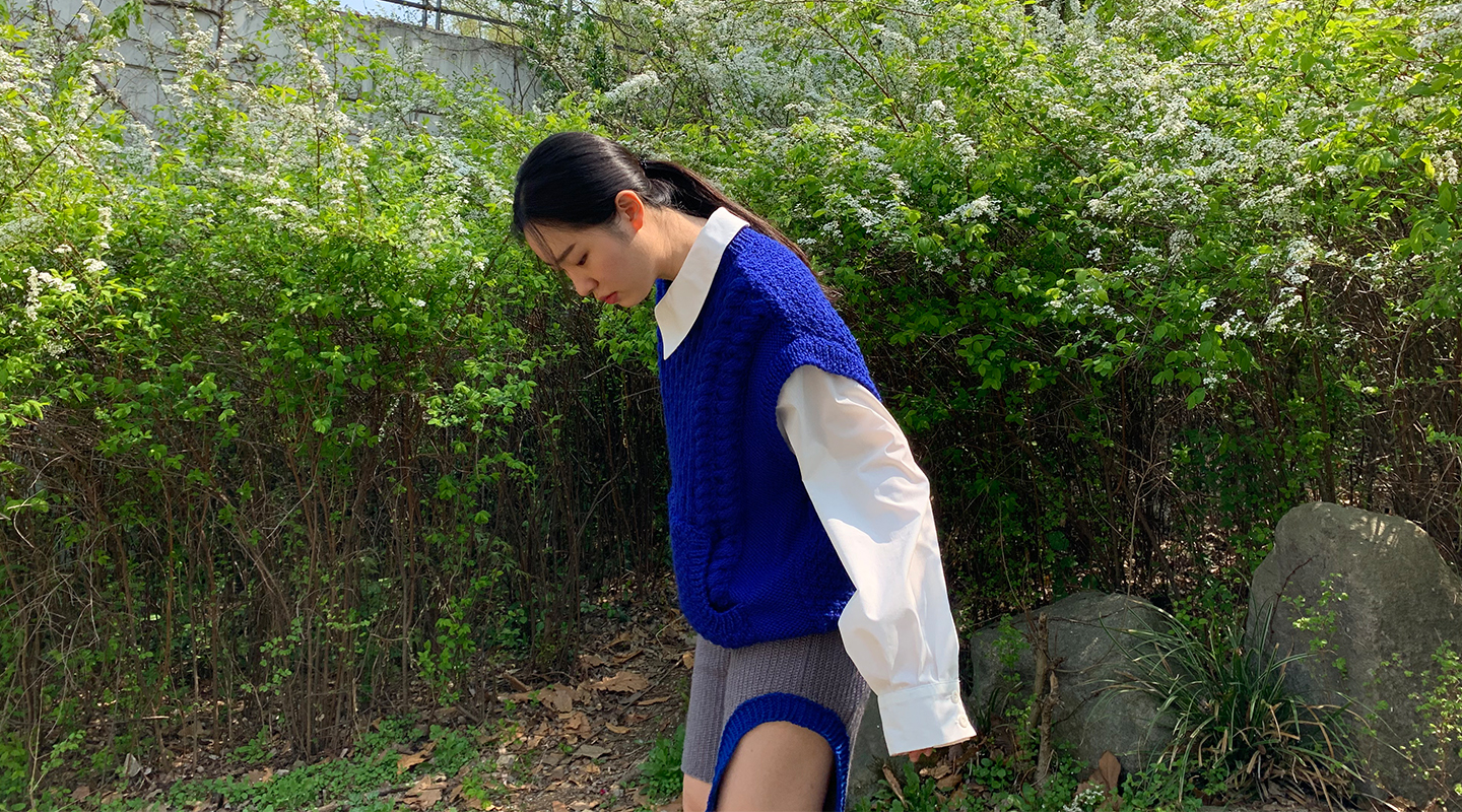 The side of the sweater details an attached woven collar and oversize sleeve.