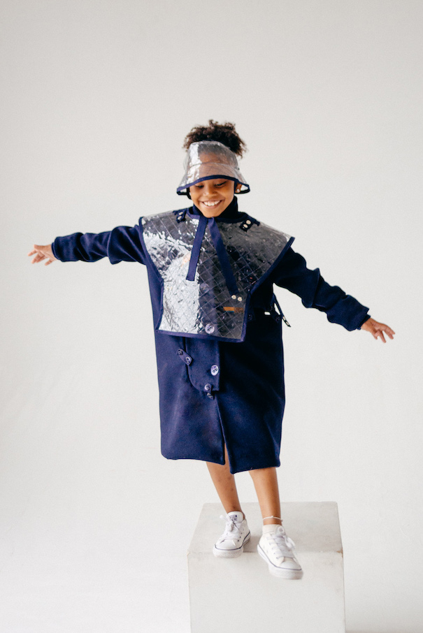 The model is wearing a patched wool trench coat with a quilted vinyl poncho and hat layered on top.