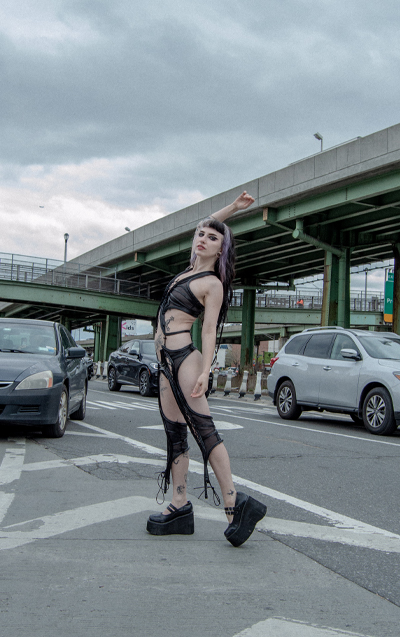 Model standing in the middle of the road, raising her right hand in the air.
