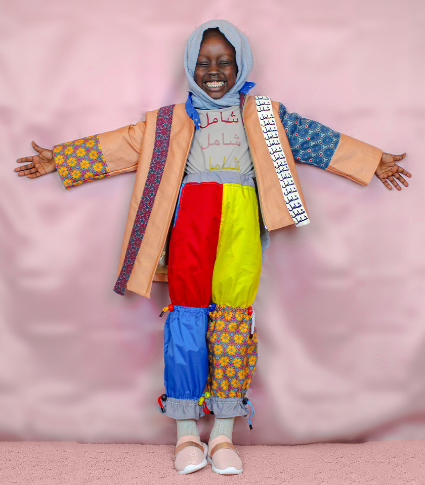 """Color blocked asymmetrical jacket, windbreaker pants, and undershirt. The shirt underneath the jacket and the white strap have Arabic letters that translate to the word """"Inclusive""""."""