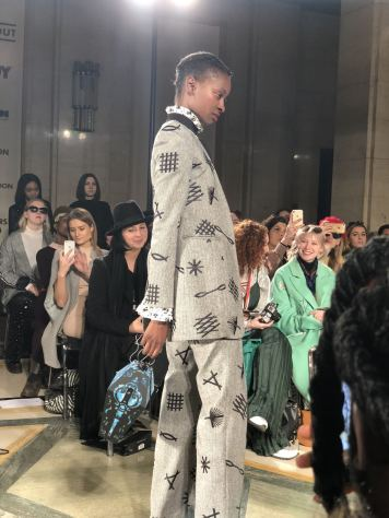 STARSICA FW18 LONDON FASHION WEEK a model on the runway in a grey suit covered in semiotic symbols as a nod to the Mad King