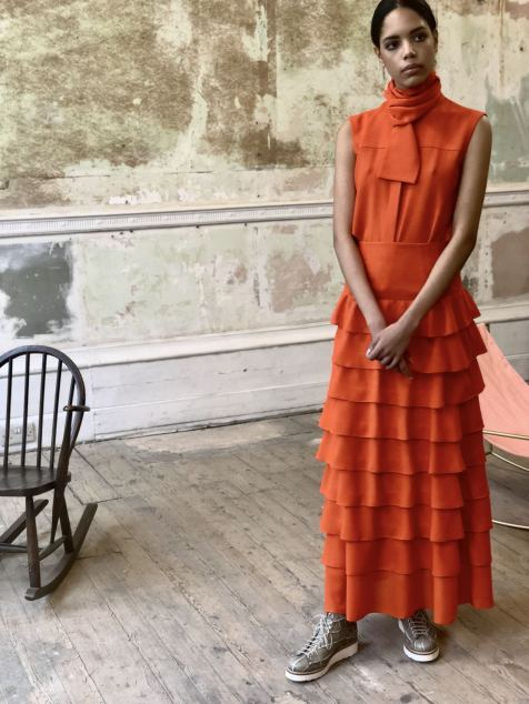 Merchant Archive FW18 LFW a model in an orange tiered dress