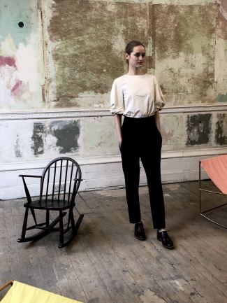 Merchant Archive FW18 LFW a model next to a rocking chair waiting a simple preppy look comprising a black trouser, white tee and brogues