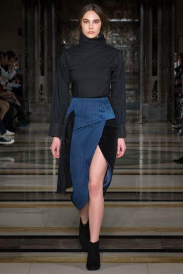 A model wears a denim wrap over skirt on the runway for SOE Jakarta at london Fashion Week FW18