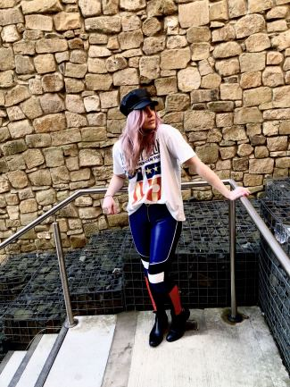 Pixie tenenbaum wearing the GIGI x TOMMY leather speed motocross style pants with a Led Zepplin tee and a baker boy hat looking away from the camera