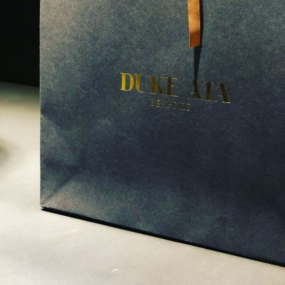 Aclose up image of a Duke Ata bag embossed in gold lettering on a shelf in the Duke Ata Clubhouse