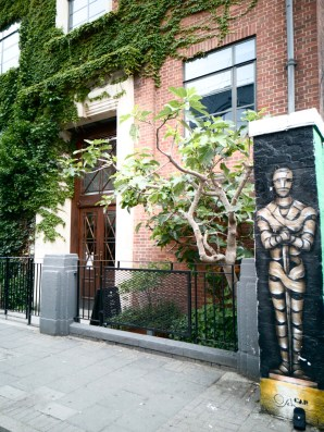 Street Art in Shoreditch: A house covered in ivy with double doors and a thin column wall painted with a knight