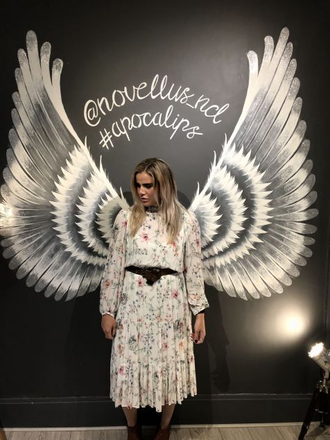 Blogger Pixie Tenenbaum standing in front of Angel wings painted on a dark grey feature wall in the new Novellus Aesthetics clinic room at 1 Benton Terrace in Jesmond. Glitter tipped wings lit up by a cinema type floor lamp featuring the words Novellus newcastle and #Apocalips. taken for Fashion Voyeur blog