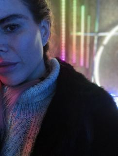 An image taken from the 2018 installation #MulberryLights at 100 Regent Street from fashion brand Mulberry as part of their Christmas campaign featuring Blogger Pixie Tenenbaum in the foregrounf and some multi-coloured lights in the background. Fashion Voyeur Blog