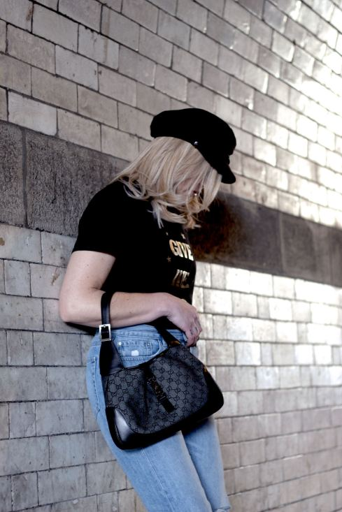 Blogger Pixie Tenenbaum posing in a subway in Newcastle with a Gucci Jackie O bag looking down. She's wearing pale blue wide leg jeans and a black tee with a baker boy hat. Photographed by Megan Scott