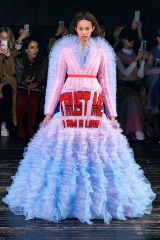 "a model in the Viktor & Rolf Spring 2019 Couture runway show in Paris featuring lots of tulle dresses bearing slogans, this one says ""Trust Me I'm An Alien"""