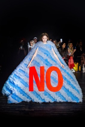 "a model in the Viktor & Rolf Spring 2019 Couture runway show in Paris featuring lots of tulle dresses bearing slogans, this one says ""NO"" in absolutely huge lettering"