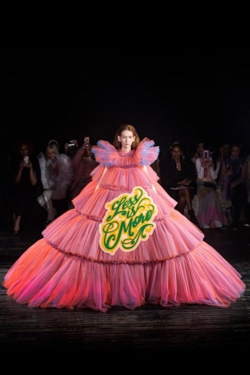 "a model in the Viktor & Rolf Spring 2019 Couture runway show in Paris featuring lots of tulle dresses bearing slogans, this one says ""Less is More"""