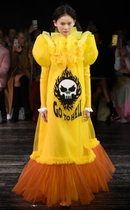 "a model in the Viktor & Rolf Spring 2019 Couture runway show in Paris featuring lots of tulle dresses bearing slogans, this one says ""Go To Hell"""