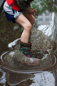 Child's legs in shorts and rain boots jumping in large puddle
