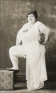 Old sepia photo of a large woman in a provocative pose in her underwear