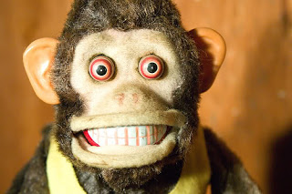 Face of a toy monkey grinning with staring red ringed eyes