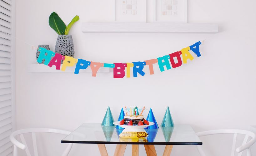 Room set up for a birthday with bunting, party hats and a cake.