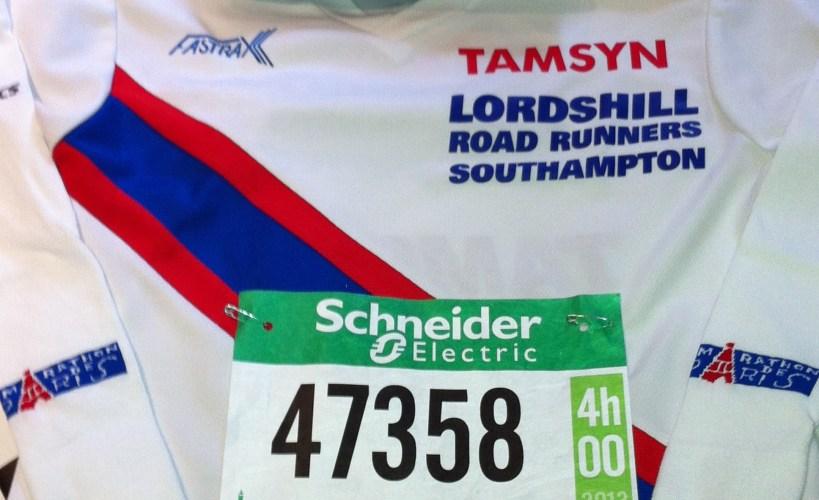 Flatlay of club t-shirt, race number, headband and arm warmers ready for Paris Marathon