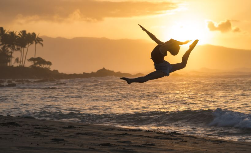 Woman doing a split leap on the beach in Hawaii