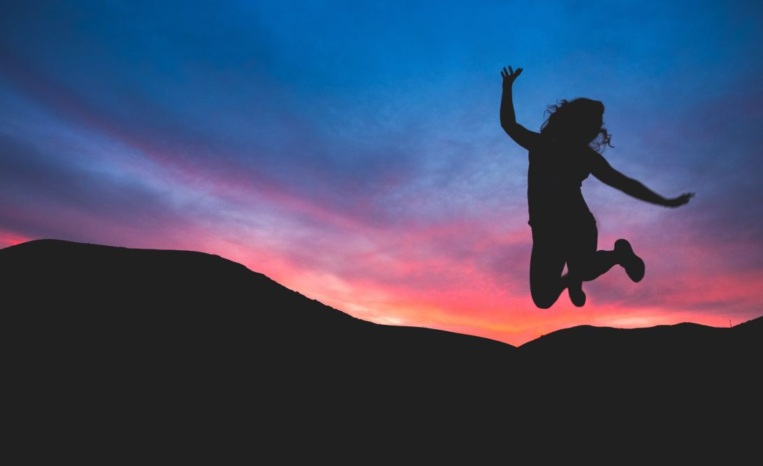 Silhouette of person jumping against a colourful dawn sky.