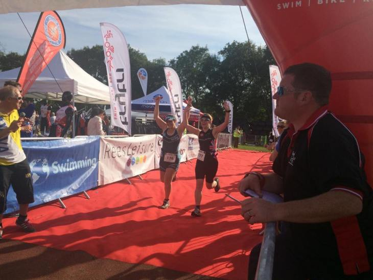 Tamsyn and Teri running across the finish line at HOWSC100 together.