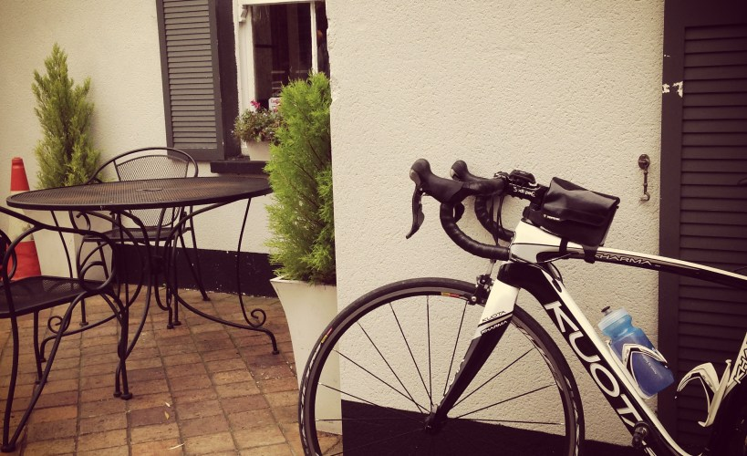 Tamsyn's Kuota Kharma parked by a cafe table.