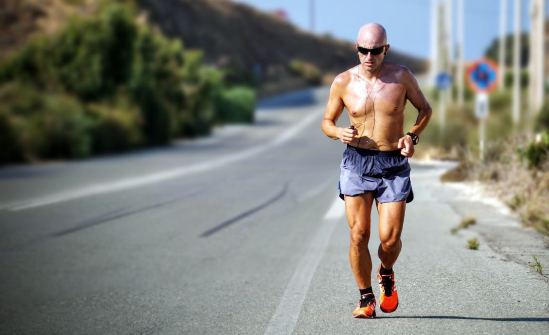 Man running shirtless by an empty road