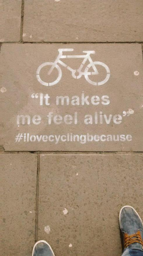 "Stencil saying ""I love cycling because it makes me feel alive"""