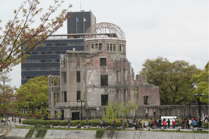 The A-bomb dome in Hiroshima. Half of the building stands and there is a metal dome on top of the building. Many tourists can be seen next to the building.