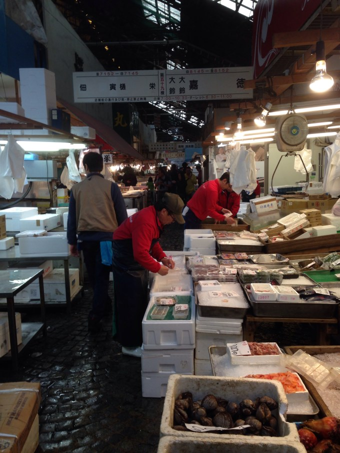 People working in Tsukiji fish market. There are polystyrene crates of diferent kinds of fish around them.