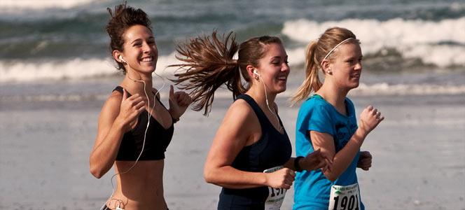Three women running on the beach whilst listening to music