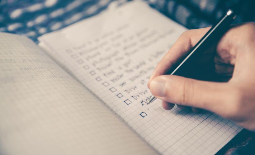 A person writing a check list