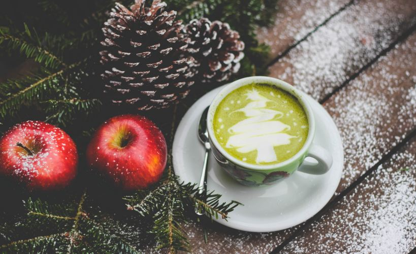 Healthy festive soup. Green soup in a mug wih cream in the shape of a Christmas tree, by some red apples, pine cones and fir branches.