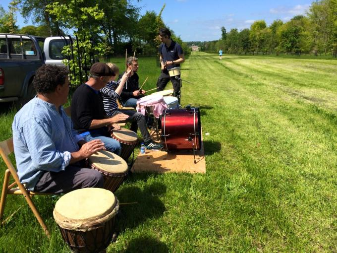 People playing bongos and drums in the sunshine.