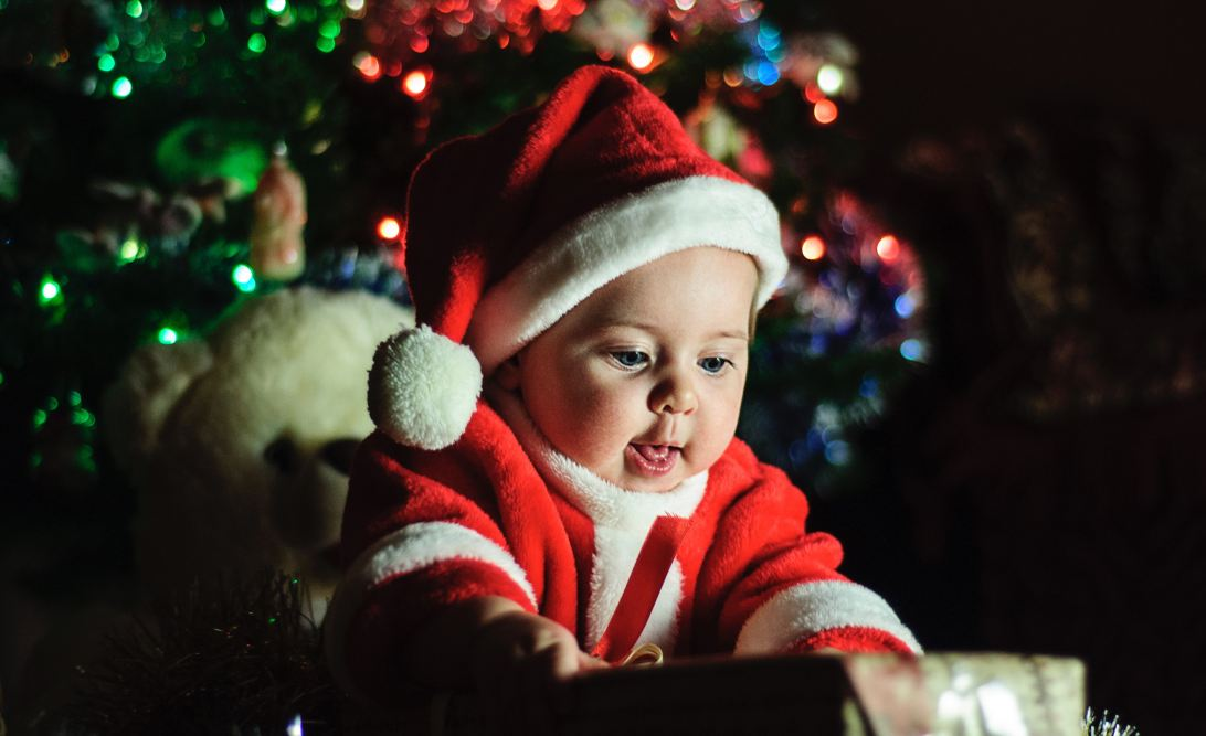 Baby dressed as Santa opening a present