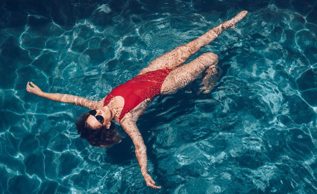 Woman floating on her back in a swimming pool.