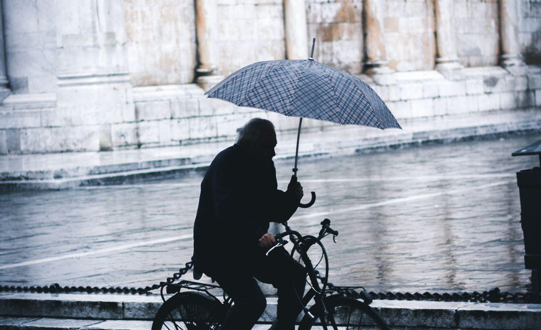 A cyclist holding an umbrella