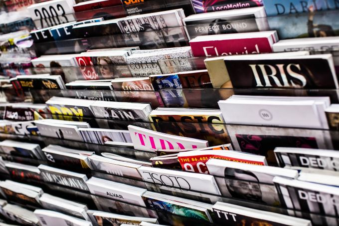 Close up of a magazine stand with magazines on it.