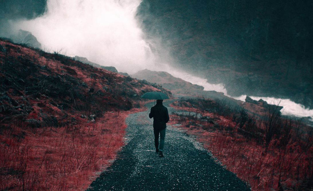 Be tougher than your life is. A person walking down a stormy road