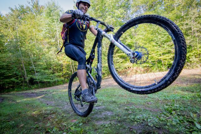 Jon Wilson pulling a wheelie on his mountain bike