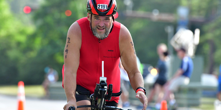 Large man in a red cycling jersey riding a bike.