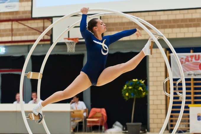 Woman wearing a leotard doing the splits in the centre of a large metal wheel.
