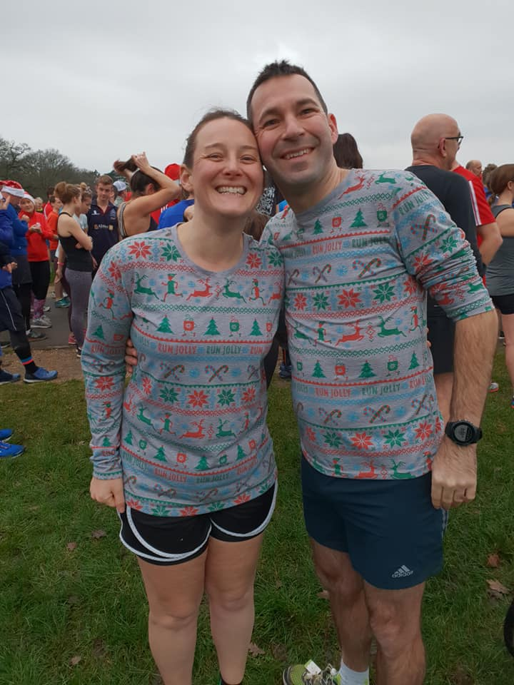 Tamsyn and Stuart wearing matching Christmas running tops. Photo taken before the start of parkrun on Christmas Day 2018.