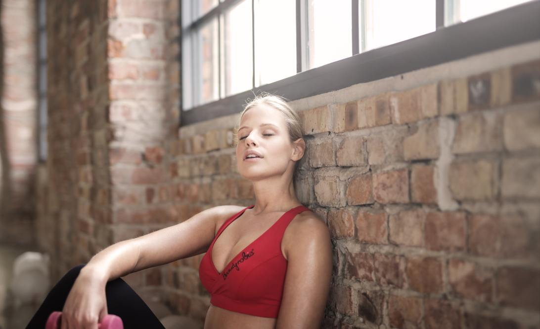Woman in a red crop top leaning against a brick wall in an exercise studio with a dumbbell in her hand