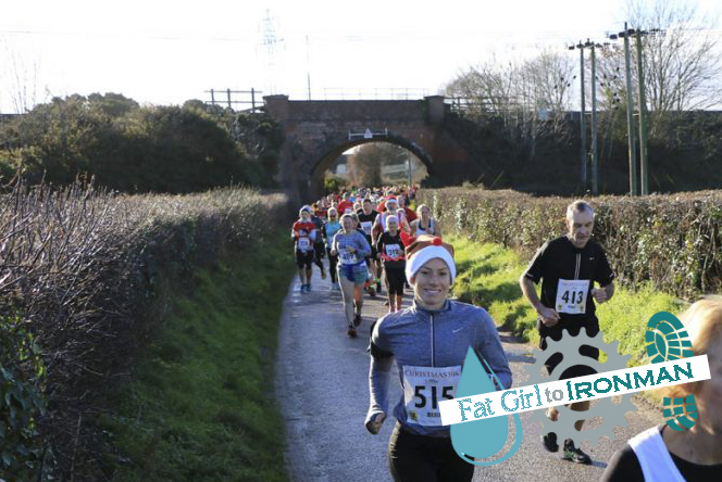 A large group of runners on a country lane.